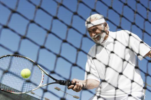 Happy senior man in sports clothing playing tennis