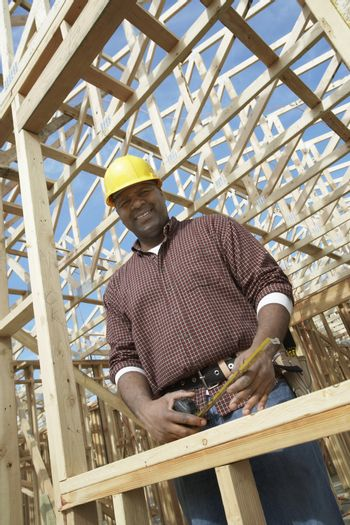 Low angle view portrait of an engineer holding a measuring tape in framework at construction site