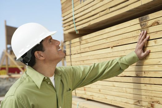 Side view of a smiling construction worker in hardhat inspecting lumber on job site