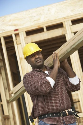 African American construction worker carrying lumber on job site