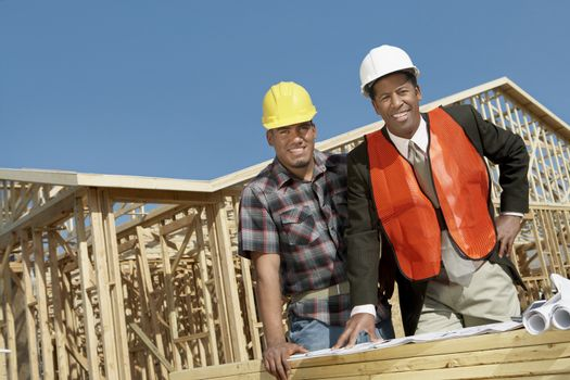 Portrait of two architects with blueprint standing in front of framework at construction site