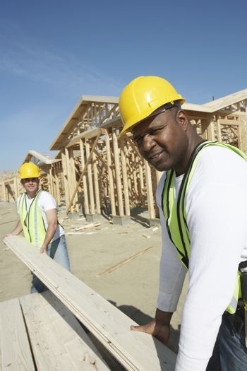 Two multiethnic construction workers stacking timber at site