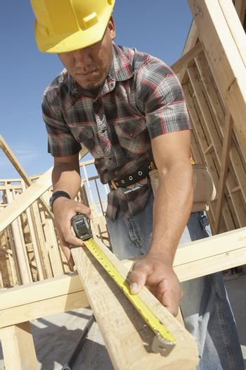 Low angle view of a construction worker measuring timber