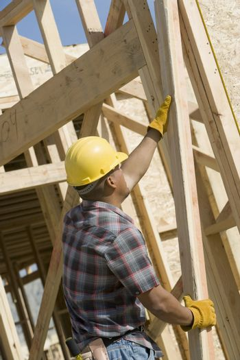 Side view of a man holding a wood beam at construction site