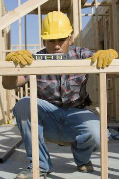 Male architect reading level measurement on construction site