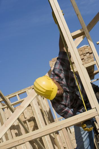 Worker measuring a wooden beam at construction site