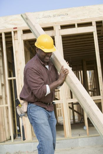 Construction worker carrying wooden plank
