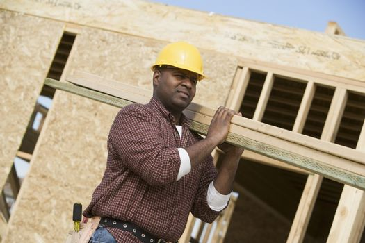 Worker carrying wooden beam on shoulder at construction site