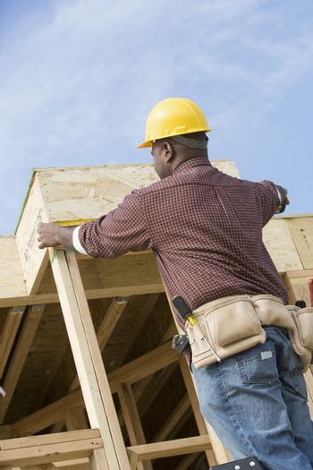 Rear view of male worker measuring a wooden beam at construction site
