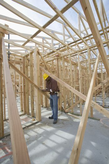 Full length view of a man measuring wooden beam in framework at construction site