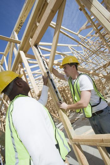 Workers measuring framework at construction site
