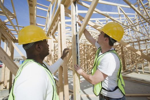 Workers measuring wooden beam at construction site