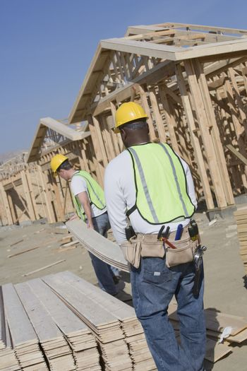Manual workers carrying wooden beam at construction site