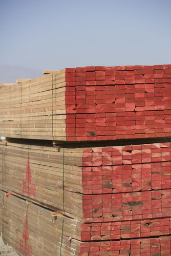 Stack of wooden beams against clear sky