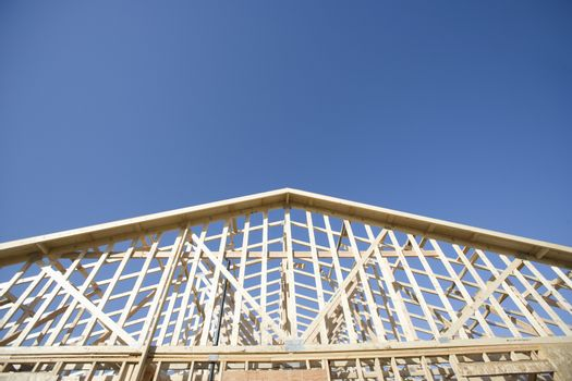 Framework of house under construction against clear sky