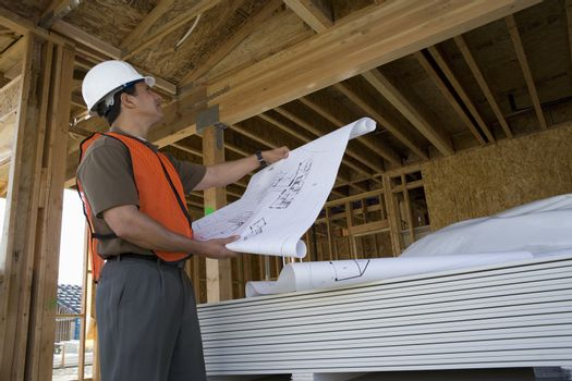 Architect with blueprint looking at framework in construction site