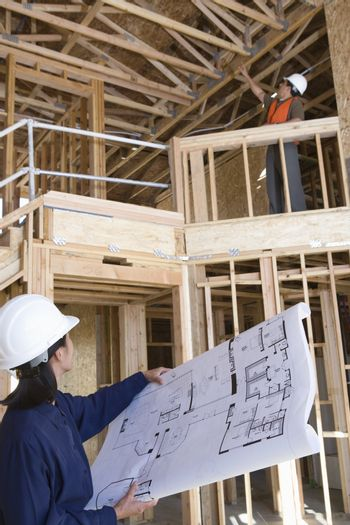 Foreman examining framework with female engineer holding blueprint at construction site