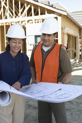 Architects with blueprint at construction site