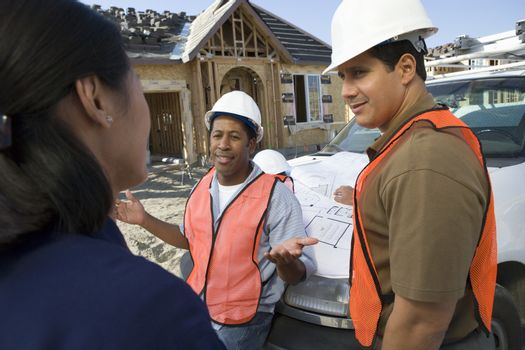 Female architect in discussion with co-workers at construction site