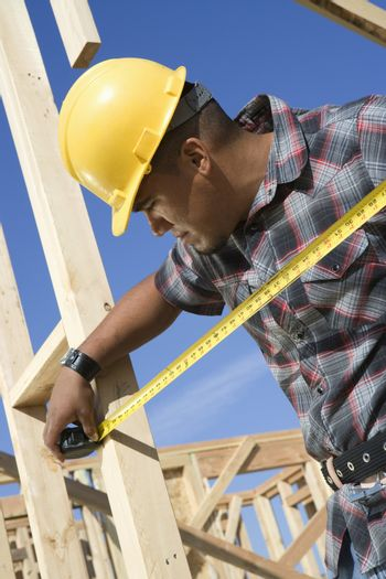 Supervisor measuring framework with measure tape at construction site