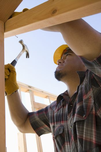 Man hammering nail to wooden beam at construction site