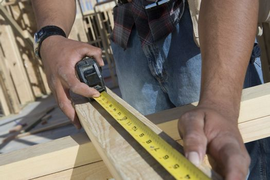 Extreme closeup of hands measuring wooden beam with measure tape