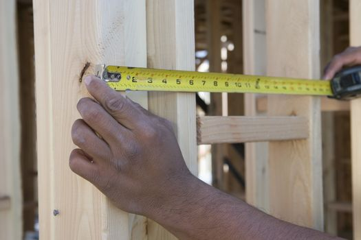 Closeup of hands measuring between boards with tape measure at construction site