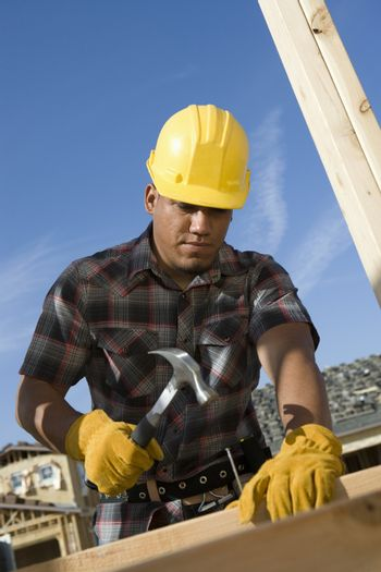 Worker hammering nail into plank at construction site