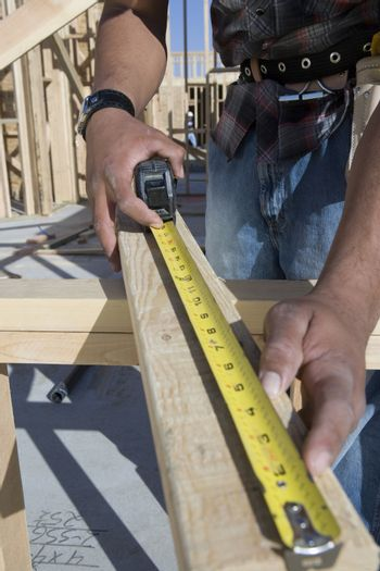 Closeup of a man measuring wooden beam with measure tape at site