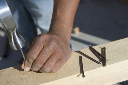 Extreme closeup of hand hammering nail to the plank