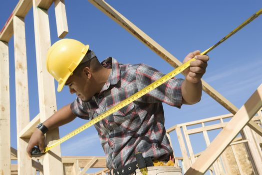 Foreman examining framework with measure tape at construction site