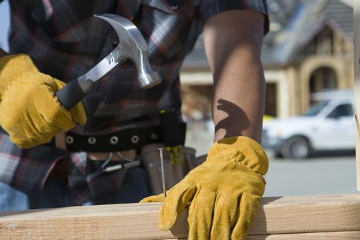 Closeup of man's hands hammering nail into wooden plank at site