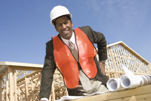 Portrait of a happy male architect standing in front of framework with blueprint at construction site