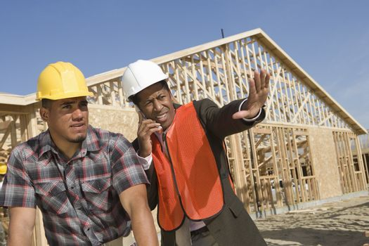 Architect on call gesturing towards site with co-worker looking away at construction site