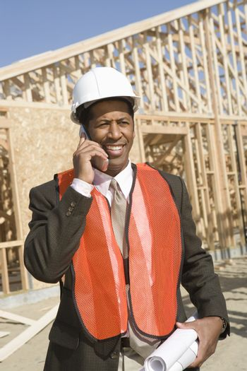 Male architect on call with blueprint in front of framework at construction site