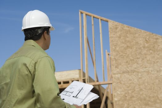 Architect looking up at framework with blueprint at construction site