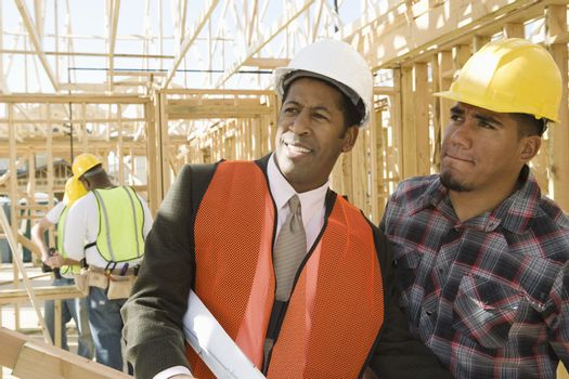 Architect with foreman inspecting framework and men working in background at construction site