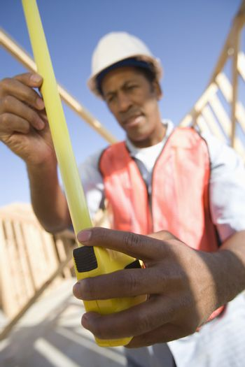 An African American male architect measuring framework with measure tape