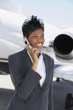 An African American businesswoman using cellphone at an airfield