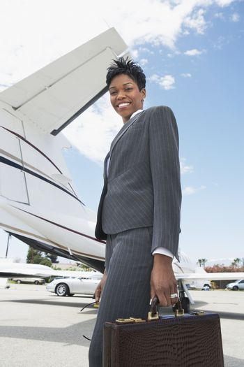 Low angle view of happy businesswoman standing on airfield with airplane in the background