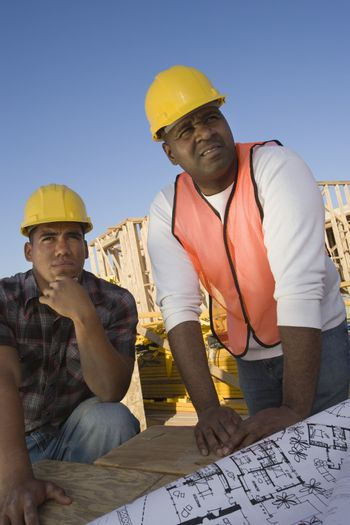 Foreman with co-worker looking at framework at construction site