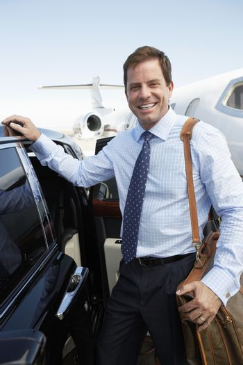 Portrait of a happy businessman with luggage by the car at airfield