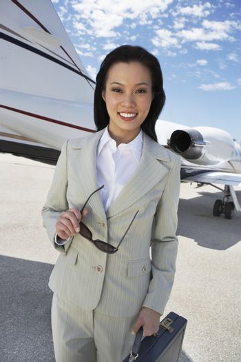 Portrait of happy businesswoman standing on airfield with aircraft in the background