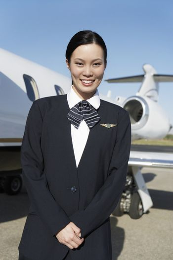 Portrait of a pretty stewardess standing on airfield with airplane in the background