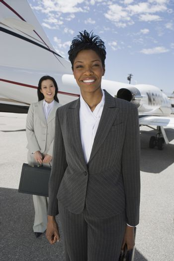 Portrait of happy business woman standing with colleague in the background at airfield