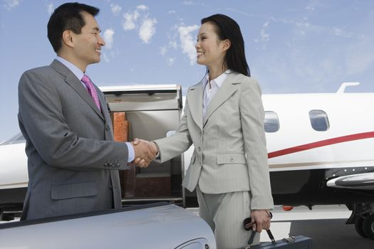 Happy Korean businesswoman and Japanese businessman meeting at the airport
