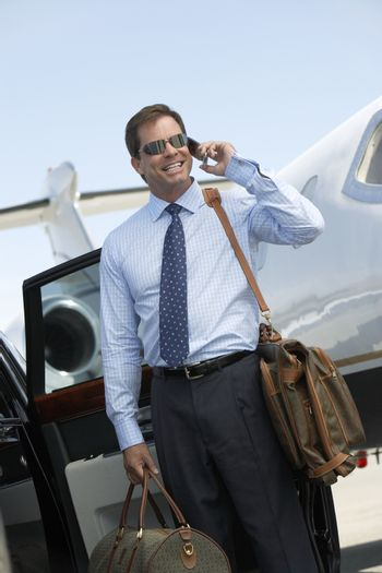 Happy businessman on a call with luggage at airfield