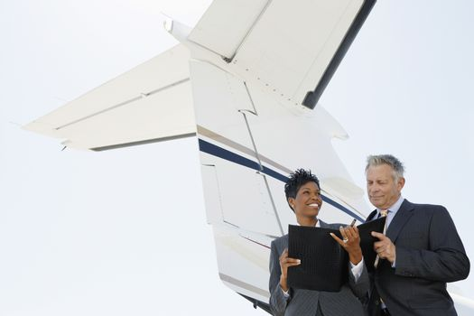 Business People Discussing Below Wing Of Private Jet
