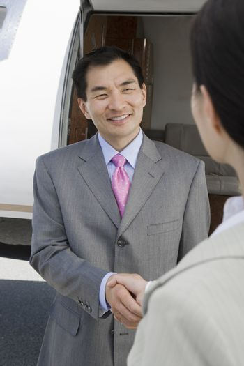Business people handshake by private plane at airfield