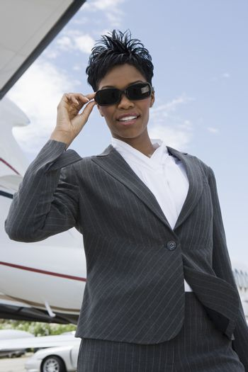 Low angle view of successful African American businesswoman standing at airfield